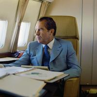 President Richard Nixon seated on board Air Force One en route to China.